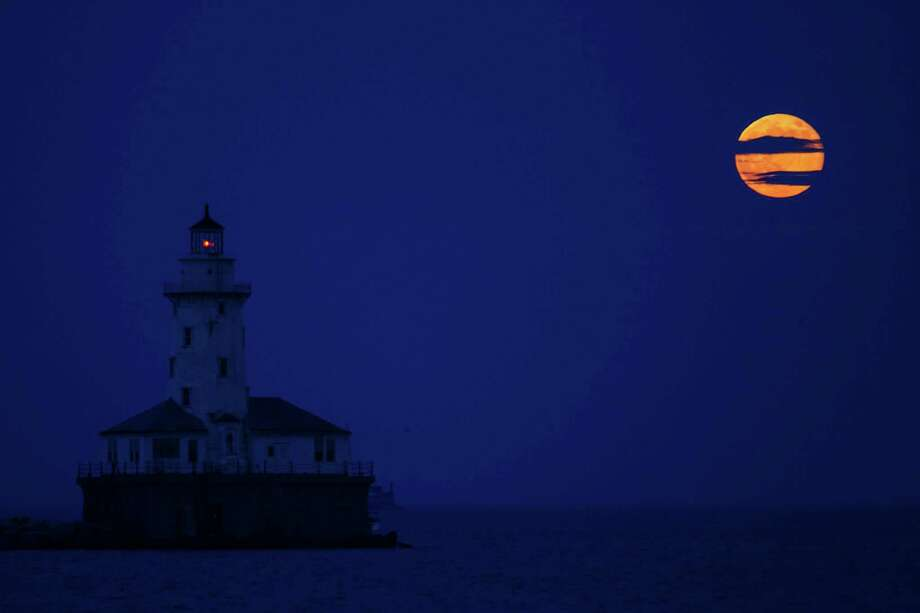 The moon rises next to the Chicago Harbor Lighthouse, Sunday in Chicago. The so-called supermoon appeared up to 14 percent larger than normal this weekend as our celestial neighbor swung closer to Earth, reaching its closest distance early Sunday morning.  Photo: Scott Eisen, Associated Press / AP