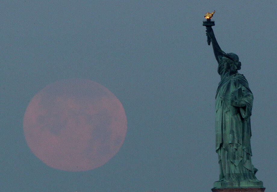 "A supermoon sets near the Statue of Liberty, Sunday, June 23, 2013, in New York. The larger than normal moon called the ""Supermoon"" happens only once this year as the moon on its elliptical orbit is at its closest point to earth and is 13.5 percent larger than usual. Photo: Julio Cortez, Associated Press / AP"