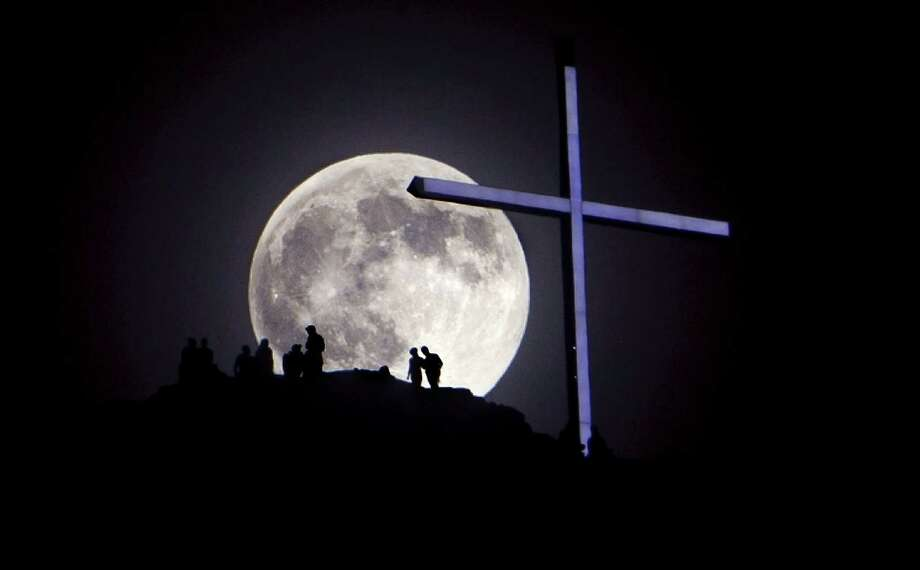 "A ""supermoon"" rises over Table Rock and lighted cross in Boise, Idaho on Saturday, June 22, 2013.  Photo: Kyle Green, McClatchy-Tribune News Service / Idaho Statesman"