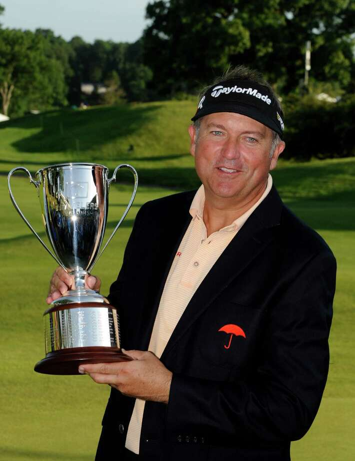Ken Duke holds the trophy after winning the Travelers Championship golf tournament in Cromwell, Conn., Sunday, June 23, 2013. Duke won the tournament with a birdie on the second playoff hole. (AP Photo/Fred Beckham) Photo: Fred Beckham