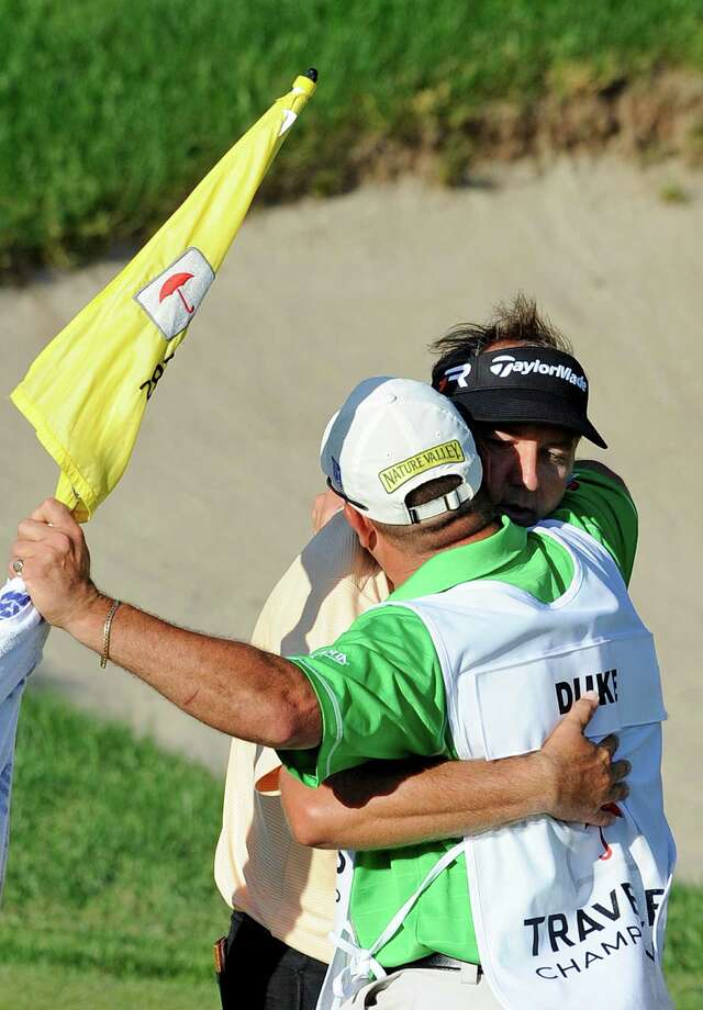 Ken Duke celebrates, right, with his caddie after winning the Travelers Championship golf tournament in Cromwell, Conn., Sunday, June 23, 2013. Duke won the second playoff hole against Chris Stroud. (AP Photo/Fred Beckham) Photo: Fred Beckham, FRE / FR153656 AP