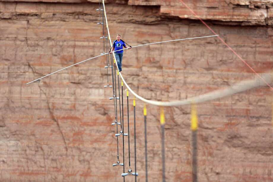 In this photo provided by the Discovery Channel, aerialist Nik Wallenda walks a 2-inch-thick steel cable taking him a quarter mile over the Little Colorado River Gorge, Ariz. on Sunday, June 23, 2013. The daredevil successfully traversed the tightrope strung 1,500 feet above the chasm near the Grand Canyon in just more than 22 minutes, pausing and crouching twice as winds whipped around him and the cable swayed. Photo: AP