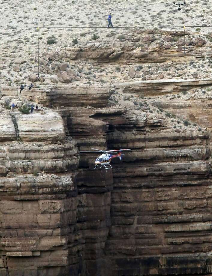 Daredevil Nik Wallenda crosses a tightrope 1,500 feet above the Little Colorado River Gorge Sunday, June 23, 2013, on the Navajo reservation outside the boundaries of Grand Canyon National Park. (AP Photo/Rick Bowmer) Photo: Rick Bowmer, Associated Press