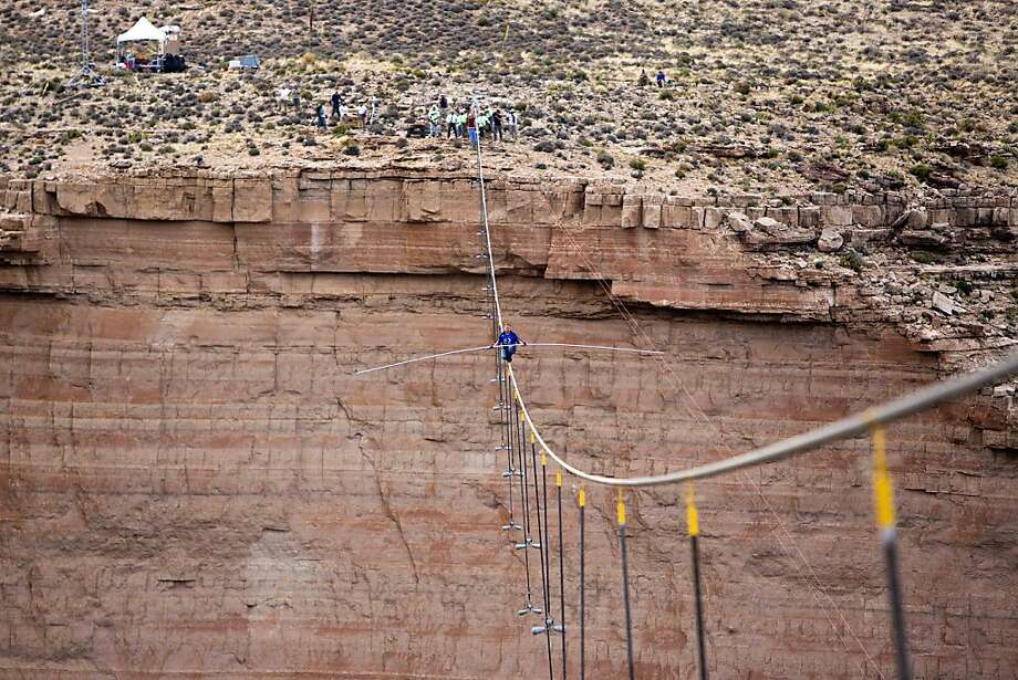 Aerialist Nik Wallenda pauses during his quarter mile walk over the Little Colorado River Gorge in northeastern Arizona on Sunday, June 23, 2013. The daredevil successfully traversed a tightrope strung 1,500 feet above the chasm near the Grand Canyon in just more than 22 minutes, pausing and crouching twice as winds whipped around him and the cable swayed. (AP Photos/Discovery Channel, Tiffany Brown) Photo: Tiffany Brown, Associated Press