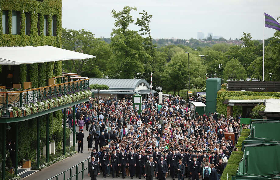 Tournament stewards escort the fans into the grounds on day one of the Wimbledon Lawn Tennis Championships at the All England Lawn Tennis and Croquet Club on June 24, 2013 in London. Photo: Dan Kitwood, Getty Images / 2013 Getty Images