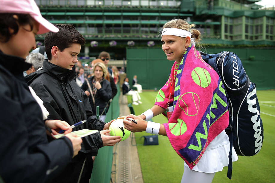 Lucie Safarova of Czech Republic signs autographs for fans aftrer her Ladies' Singles first round match against Lauren Davis of United States of America on day one of the Wimbledon Lawn Tennis Championships at the All England Lawn Tennis and Croquet Club on June 24, 2013 in London. Photo: Dan Kitwood, Getty Images / 2013 Getty Images