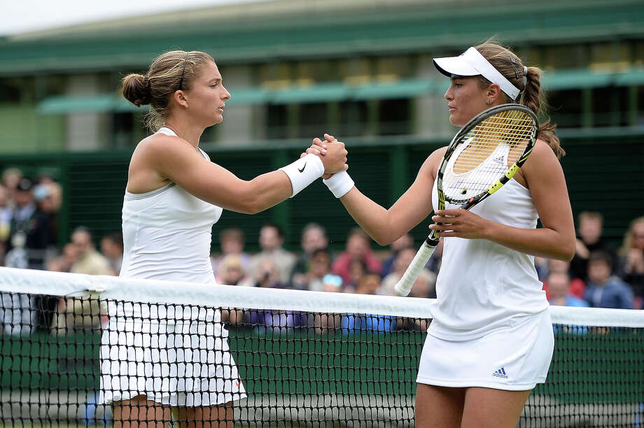 Sara Errani of Italy shakes hands at the net with Monica Puig of Puerto Rico after their Ladies' Singles first round match on day one of the Wimbledon Lawn Tennis Championships at the All England Lawn Tennis and Croquet Club on June 24, 2013 in London. Photo: Dennis Grombkowski, Getty Images / 2013 Getty Images
