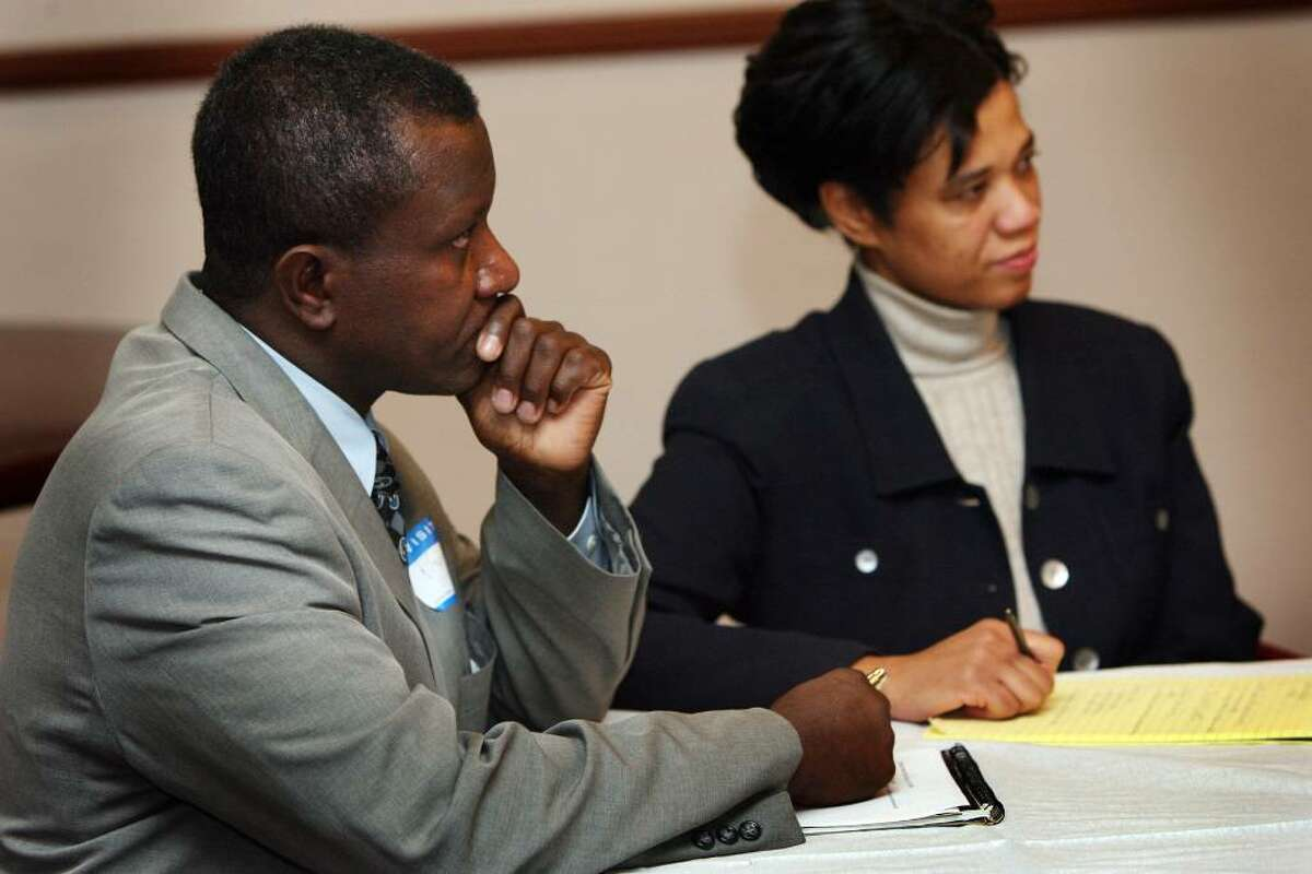 Pierre D'Haiti, left, and his wife, Shirley, listen to Bridgeport city employees and relief organization members gathered at a roundtable meeting on Friday, Jan 15, 2010 to discuss local relief efforts for victims of Haiti's earthquake.