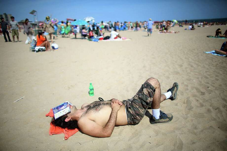 NEW YORK, NY - JUNE 22: A man sleeps on the beach during the 2013 Mermaid Parade at Coney Island on June 22, 2013 in the Brooklyn borough of New York City. Coney Island was hard hit by Superstorm Sandy but parade organizers, whose offices were flooded, were able to raise $100,000 on Kickstarter to fund the parade. The Mermaid Parade began in 1983 and features participants dressed as mermaids and other sea creatures while paying homage to the former tradition of the Coney Island Mardi Gras, which ran annually in the early fall from 1903-1954. Photo: Mario Tama, Getty Images / 2013 Getty Images