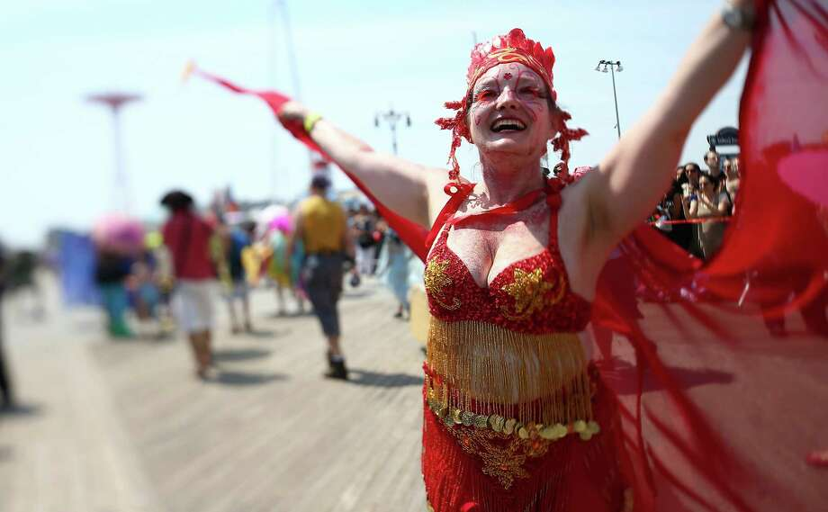 NEW YORK, NY - JUNE 22:  (EDITORS NOTE: Image was created using a variable planed lens.) A reveler marches during the 2013 Mermaid Parade at Coney Island on June 22, 2013 in the Brooklyn borough of New York City. Coney Island was hard hit by Superstorm Sandy but parade organizers, whose offices were flooded, were able to raise $100,000 on Kickstarter to fund the parade. The Mermaid Parade began in 1983 and features participants dressed as mermaids and other sea creatures while paying homage to the former tradition of the Coney Island Mardi Gras, which ran annually in the early fall from 1903-1954. Photo: Mario Tama, Getty Images / 2013 Getty Images