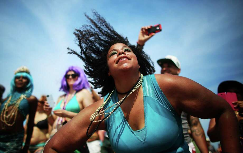 NEW YORK, NY - JUNE 22:  Revelers dance on the beach at the 2013 Mermaid Parade at Coney Island on June 22, 2013 in the Brooklyn borough of New York City. Coney Island was hard hit by Superstorm Sandy but parade organizers, whose offices were flooded, were able to raise $100,000 on Kickstarter to fund the parade. The Mermaid Parade began in 1983 and features participants dressed as mermaids and other sea creatures while paying homage to the former tradition of the Coney Island Mardi Gras, which ran annually in the early fall from 1903-1954. Photo: Mario Tama, Getty Images / 2013 Getty Images