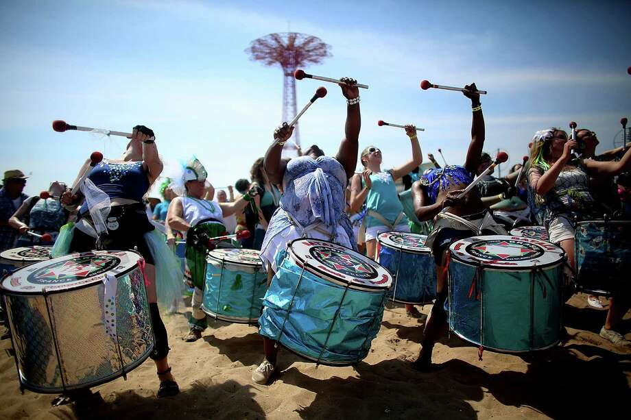 NEW YORK, NY - JUNE 22:  Musicians perform on the beach at the 2013 Mermaid Parade at Coney Island on June 22, 2013 in the Brooklyn borough of New York City. Coney Island was hard hit by Superstorm Sandy but parade organizers, whose offices were flooded, were able to raise $100,000 on Kickstarter to fund the parade. The Mermaid Parade began in 1983 and features participants dressed as mermaids and other sea creatures while paying homage to the former tradition of the Coney Island Mardi Gras which ran annually in the early fall from 1903-1954. Photo: Mario Tama, Getty Images / 2013 Getty Images