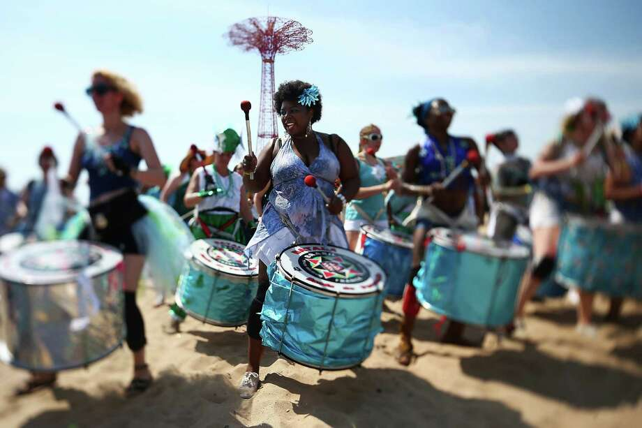 NEW YORK, NY - JUNE 22:  (EDITORS NOTE: Image was created using a variable planed lens.) Musicians from Batala NYC perform on the beach at the 2013 Mermaid Parade at Coney Island on June 22, 2013 in the Brooklyn borough of New York City. Coney Island was hard hit by Superstorm Sandy but parade organizers, whose offices were flooded, were able to raise $100,000 on Kickstarter to fund the parade. The Mermaid Parade began in 1983 and features participants dressed as mermaids and other sea creatures while paying homage to the former tradition of the Coney Island Mardi Gras, which ran annually in the early fall from 1903-1954. Photo: Mario Tama, Getty Images / 2013 Getty Images