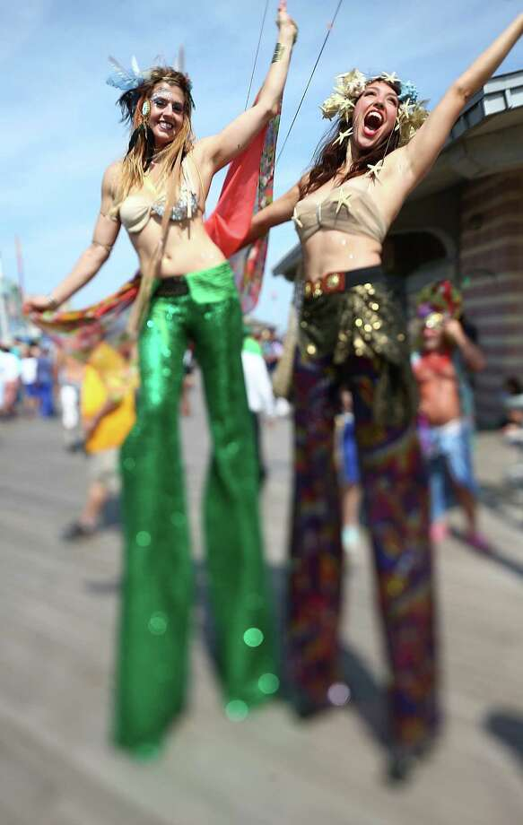 NEW YORK, NY - JUNE 22:  (EDITORS NOTE: Image was created using a variable planed lens.) Revelers pose during the 2013 Mermaid Parade at Coney Island June 22, 2013 in the Brooklyn borough of New York City. Coney Island was hard hit by Superstorm Sandy but parade organizers, whose offices were flooded, were able to raise $100,000 on Kickstarter to fund the parade. The Mermaid Parade began in 1983 and features participants dressed as mermaids and other sea creatures while paying homage to the former tradition of the Coney Island Mardi Gras which ran annually in the early fall from 1903-1954. Photo: Mario Tama, Getty Images / 2013 Getty Images