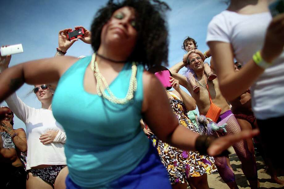 NEW YORK, NY - JUNE 22:  Revelers look on and dance on the beach at the 2013 Mermaid Parade at Coney Island on June 22, 2013 in the Brooklyn borough of New York City. Coney Island was hard hit by Superstorm Sandy but parade organizers, whose offices were flooded, were able to raise $100,000 on Kickstarter to fund the parade. The Mermaid Parade began in 1983 and features participants dressed as mermaids and other sea creatures while paying homage to the former tradition of the Coney Island Mardi Gras which ran annually in the early fall from 1903-1954. Photo: Mario Tama, Getty Images / 2013 Getty Images