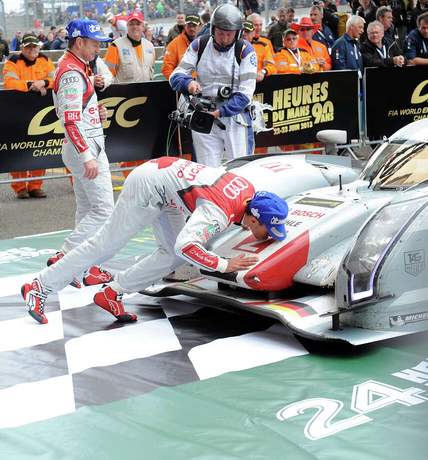 French driver Loic Duval kisses his Audi R18 E-Tron Quattro N∞2 after Danish driver Tom Kristensen crossed the finish line at the end of the 90th edition Le Mans 24 hours endurance race on June 23, 2013 in Le Mans western France. Photo: JEAN FRANCOIS MONIER, AFP/Getty Images / 2013 AFP