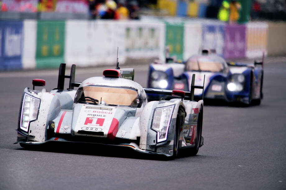 Danish driver Tom Kristensen (L), in his Audi R18 E-Tron Quattro, steers his car ahead of Swiss Sebastien Buemi's Toyota TS030 Hybrid during the 90th edition Le Mans 24 hours endurance race on June 23, 2013, in Le Mans, western France. Kristensen, 45, was part of the winning trio of drivers extending his all-time record of nine victories in the historic race but first since 2008. Audi recorded their 12th win in the Le Mans 24 hour race but it was a victory overshadowed by the death of Danish driver Allan Simonsen. Photo: ALAIN JOCARD, AFP/Getty Images / 2013 AFP