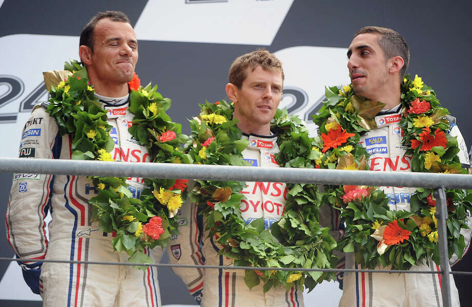 (L to R) Toyota TS030 - Hybrid N∞ 8 pilots France's Stephane Sarrazin (L), England's Anthony Davidson (C) and Switzerland's Sebastien Buemi (R) react on the podium after second place in the 90th edition of Le Mans 24 Hours endurance race on June 23, 2013, in le Mans, western France. Audi recorded their 12th win in the Le Mans 24 hours race, with the victory of Audi R18 e-tron quattro pilots Scotland's Allan McNish, Denmark's Tom Kristensen and France's Loic Duval, but it was a victory overshadowed by the death of Danish driver Allan Simonsen. Photo: JEAN FRANCOIS MONIER, AFP/Getty Images / 2013 AFP