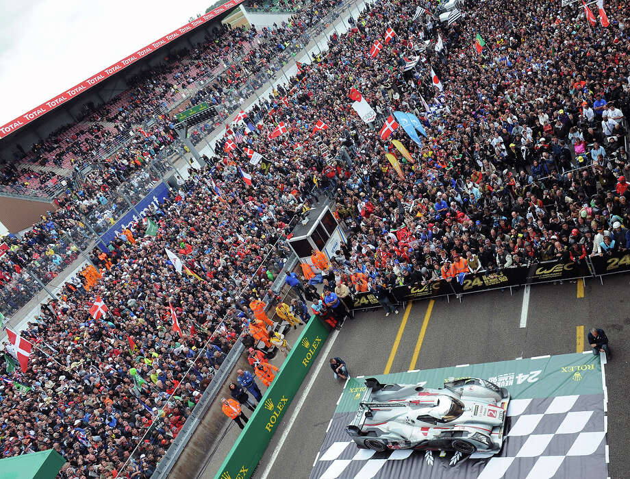 People gather to celebrate the winning car of the 90th edition Le Mans 24 hours endurance race, an Audi R18 e-tron quattro, on June 23, 2013, in Le Mans, western France. Audi recorded their 12th win in the Le Mans 24 hour race, but it was a victory overshadowed by the death of Danish driver Allan Simonsen. Photo: AFP, AFP/Getty Images / 2013 AFP