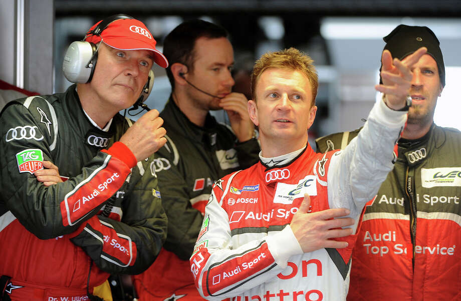 Driver Allan McNish of Scotland (R) speaks to Dr. Wolfgang Ullrich, director of Audi Sport as they stand in the pit during last lap of McNish's Danish teammate in their Audi R18 e-tron quattro during the 90th edition Le Mans 24 hours endurance race on June 23, 2013, in Le Mans, western France. Drivers of the Audi R18 e-tron quattro Allan McNish of Scotland, Tom Kristensen of Denmark and Loic Duval of France won the race, but it was a victory overshadowed by the death of Danish driver Allan Simonsen. Photo: AFP, AFP/Getty Images / 2013 AFP