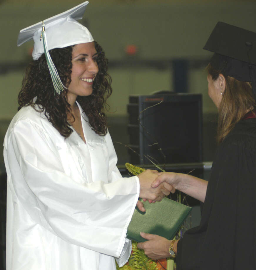 Taylor Daniels receives her diploma from Board of Education chairwoman Wendy Faulenbach during New Milford High School's commencement exercises at the O'Neill Center on the campus of Western Connecticut State University in Danbury. June 22, 2013 Photo: Norm Cummings