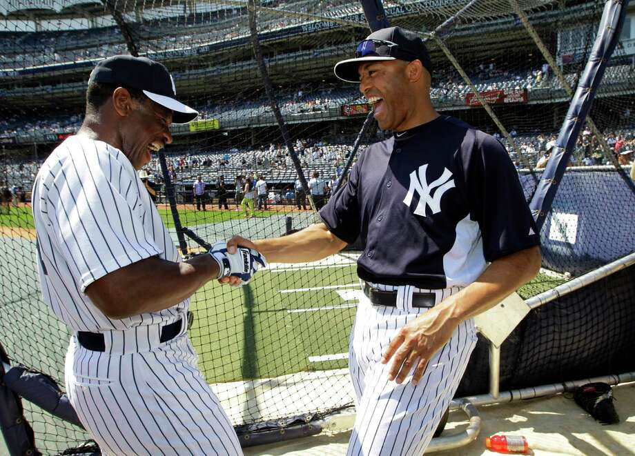 New York Yankees Rickey Henderson, left, greets Yankees relief pitcher Mariano Rivera before the Old Timers Day baseball game Sunday, June 23, 2013, in New York. Photo: Kathy Willens, AP / AP