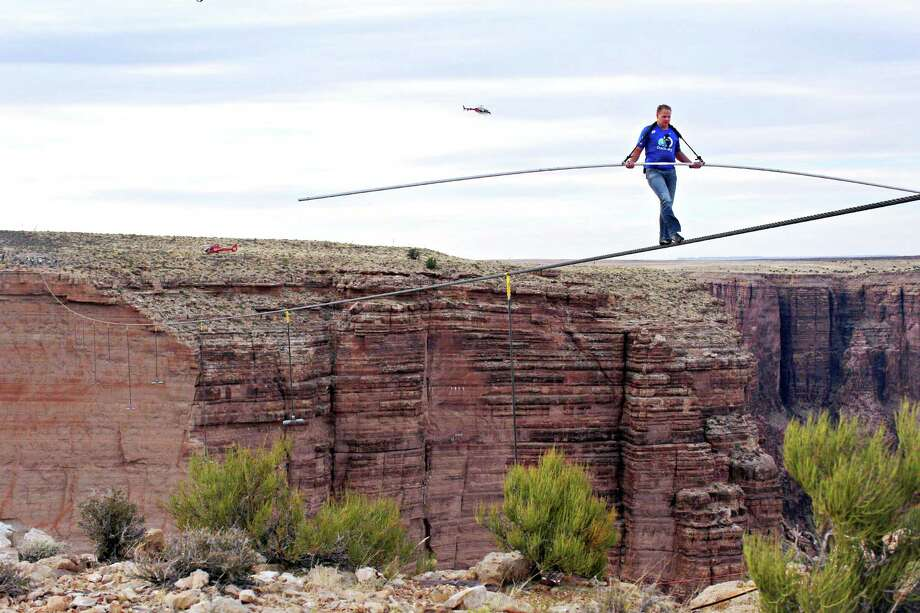 Aerialist Nik Wallenda near the end of his quarter mile walk over the Little Colorado River Gorge in northeastern Arizona on Sunday, June 23, 2013. The daredevil successfully traversed the tightrope strung 1,500 feet above the chasm near the Grand Canyon in just more than 22 minutes, pausing and crouching twice as winds whipped around him and the cable swayed. Photo: Tiffany Brown, AP / Discovery Channel