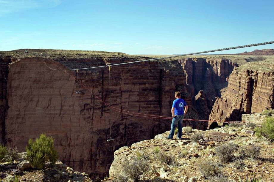 Aerialist Nik Wallenda looks across the canyon before walking a 2-inch-thick steel cable that took him a quarter mile over the Little Colorado River Gorge in northeastern Arizona on Sunday, June 23, 2013. The daredevil successfully traversed the tightrope strung 1,500 feet above the chasm near the Grand Canyon in just more than 22 minutes, pausing and crouching twice as winds whipped around him and the cable swayed. Photo: Tiffany Brown, AP / Discovery Channel