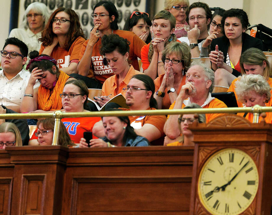 Women's rights protesters react in gallery of the House of Representative Chambers as State Rep. Jodie Laubenberg, R-Parker, works on the second reading of Senate Bill 5, the bill she sponsored, during debate on abortion held on the House floor of the State Capitol in Austin, Texas, on Sunday, June 23, 2013.  If passed, the bill would ban abortions after 20 weeks, require that they take place in surgical centers, and restrict where and when women can take abortion-inducing pills_and force 37 out of 42 abortion clinics in Texas to close and undergo millions of dollars in upgrades. (AP Photo/Statesman.com, Rodolfo Gonzalez) Photo: Rodolfo Gonzalez, MBO / Austin American-Statesman
