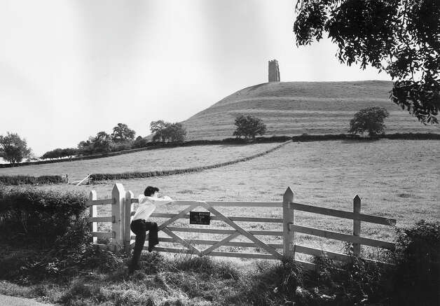 1970: A boy leaning on a gate near St Michael's Chapel on Glastonbury Tor (background) in Somerset, England. Photo: Barnard, Getty Images / Hulton Archive