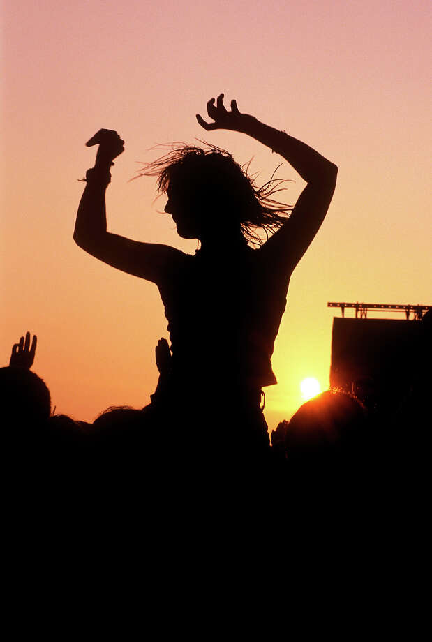 1970: A woman sitting on shoulders above crowds at sunset at Glastonbury Festival. Photo: Nicky J. Sims, Redferns / Redferns