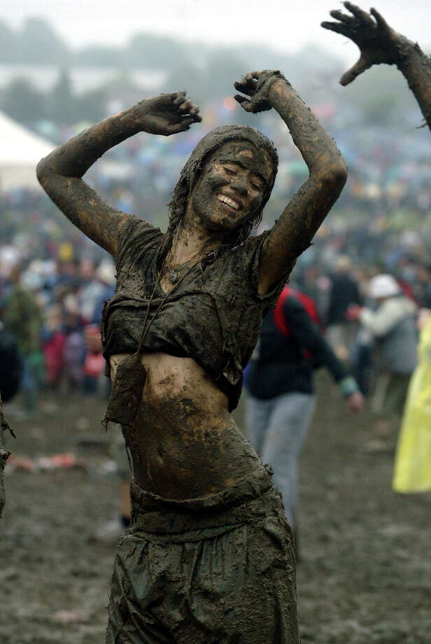 2004: Festival goers dance in the mud in front of the Pyramid stage at Worthy Farm, Pilton, Somerset, at the 2004 Glastonbury Festival, 26 June 2004. Photo: Matt Cardy, Getty Images / 2004 Getty Images