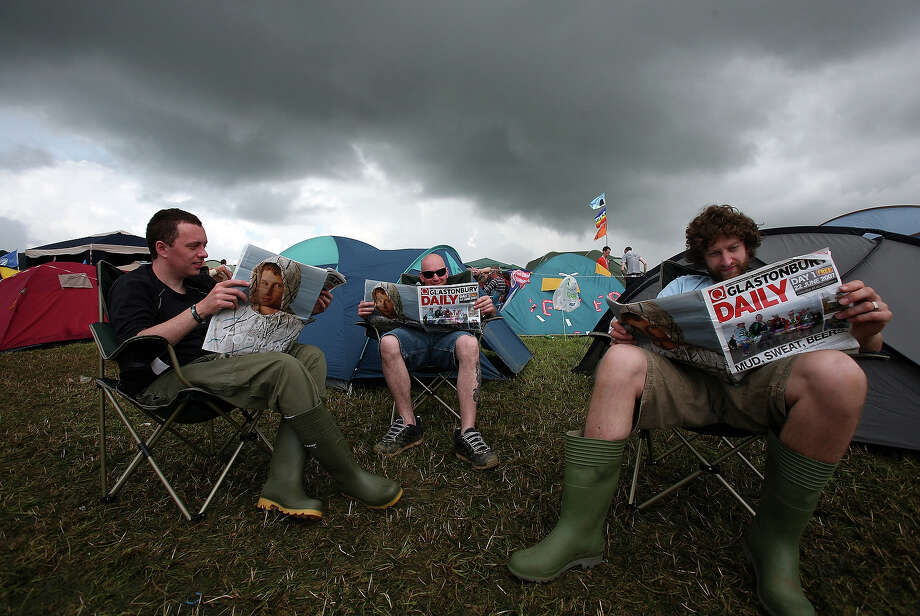 2007: Music fans read Glastonbury newspapers under rain clouds at Worthy Farm, Pilton near Glastonbury, on June 22 2007 in Somerset, England. The festival, that was started by dairy farmer Michael Eavis in 1970, has grown into the largest music festival in Europe. Photo: Matt Cardy, Getty Images / 2007 Getty Images