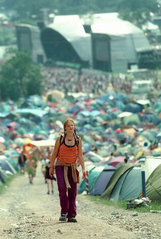 1970: A woman walking through tents in campsite at Glastonbury