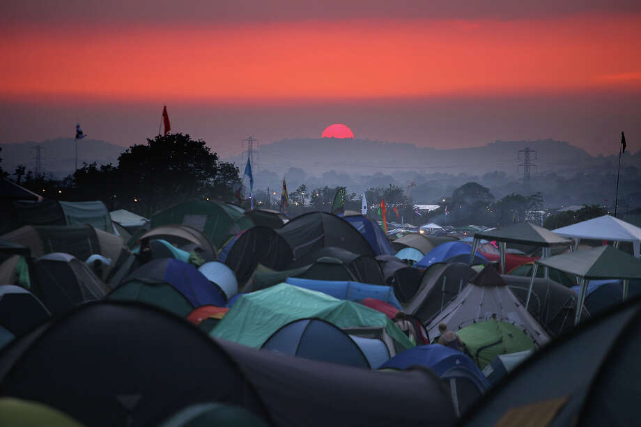 2009: The sun sets over tents at the Glastonbury Festival on June 26, 2009 in Glastonbury, England. Photo: Matt Cardy, Getty Images / 2009 Getty Images