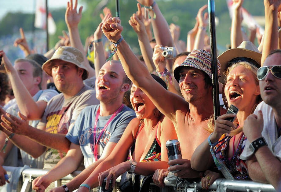 2009:  Music fans cheer during a performance by Kasabian at day three of the Glastonbury Music Festival at Glastonbury Festival site on June 27, 2009 in Glastonbury, England. Photo: Frantzesco Kangaris, Getty Images / 2009 Frantzesco Kangaris