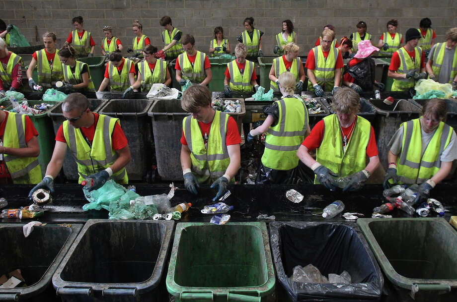 2009: Volunteer workers sort rubbish for recycling at the Glastonbury Festival recycling centre on June 29, 2009 in Glastonbury, England. Every year the festival employs a team of 1200 volunteers - who work for four, six hour shifts for a festival ticket - to sort what can be up to 2000 tons of rubbish generated during the festival. The festival recyclesf all the cans, plates, cups, plastics and food waste left by the 137,00 people. Photo: Matt Cardy, Getty Images / 2009 Getty Images