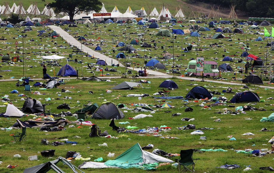 2009: People pass discarded tents and rubbish on the start of the big clear-up of the Glastonbury Festival site at Worthy Farm, Pilton on June 29, 2009 near Glastonbury, England. Photo: Matt Cardy, Getty Images / 2009 Getty Images