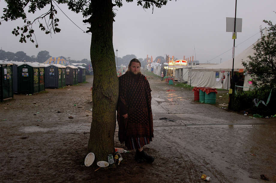 2007: A man leaning on a tree in the mud, keeping warm in a blanket, at 5am after a long night at Glastonbury. Photo: Martin Godwin, Getty Images / 2010 Getty Images