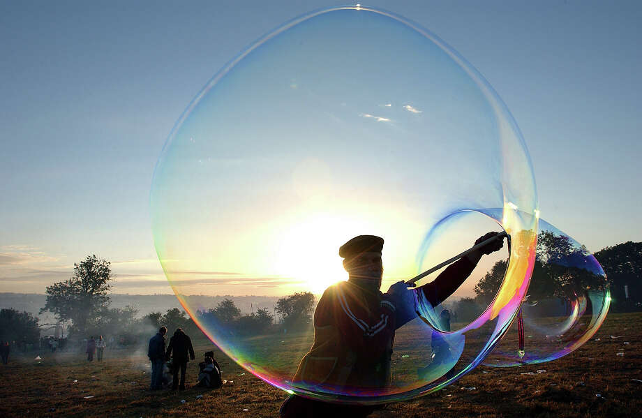 2004: A man blowing soap bubbles at the stone circle as the sun comes up at 4.30am at Glastonbury, 25th June 2004 Photo: Martin Godwin, Getty Images / 2010 Getty Images