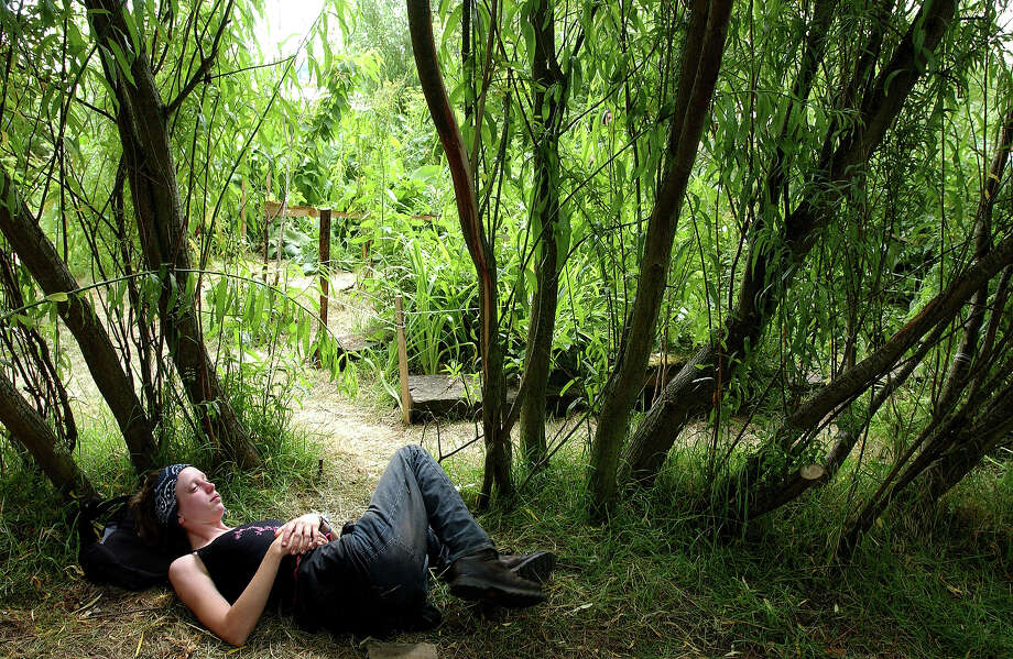 2003: A festival goer relaxing in an eco-garden by the Green Fields at Glastonbury, an oasis of calm, 29th June 2003. Photo: Martin Godwin, Getty Images / 2010 Getty Images