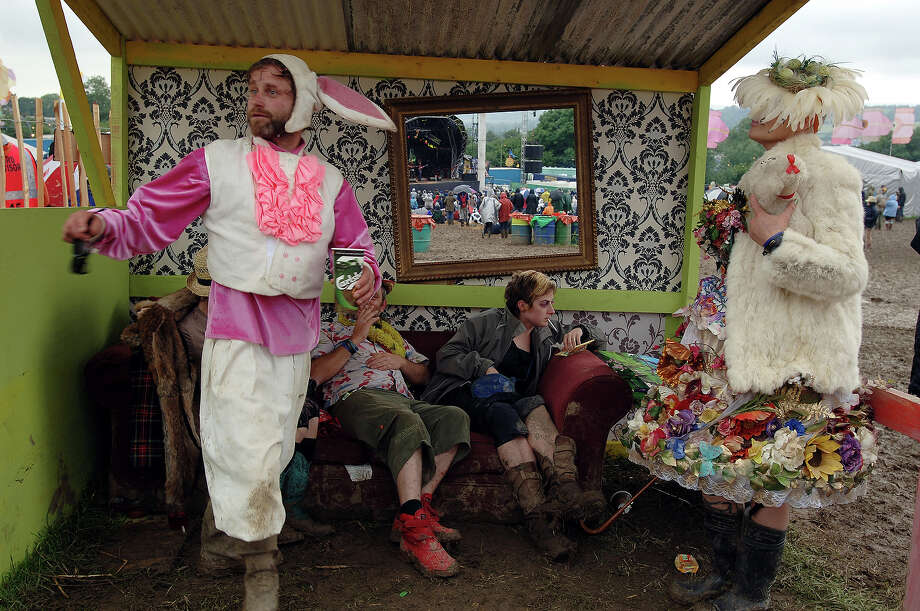 2007: A man dressed as rabbit with friends in fancy dress, relaxing at a muddy Glastonbury, with a view of the festival through a picture frame. Photo: Martin Godwin, Getty Images / 2010 Getty Images