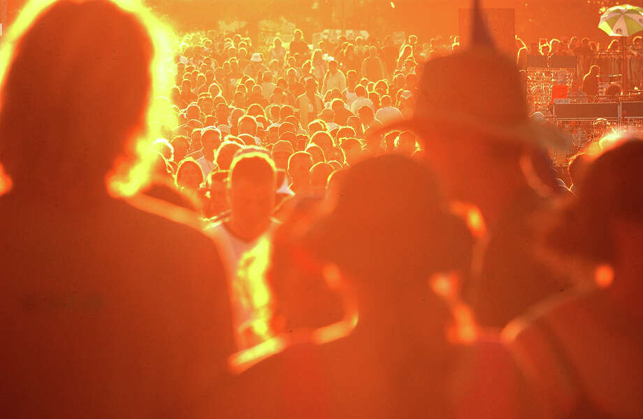 2003: Crowds of people on the move between stages as the sun goes down casting an orange glow on Glastonbury, 28th June 2003. Photo: Martin Godwin, Getty Images / 2010 Getty Images