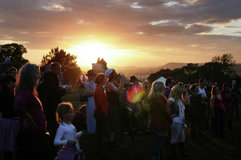 2007: Festival goers at the Stone Circle at sunset at Glastonbury, 22nd June 2007. Photo: Martin Godwin, Getty Images / 2010 Getty Images