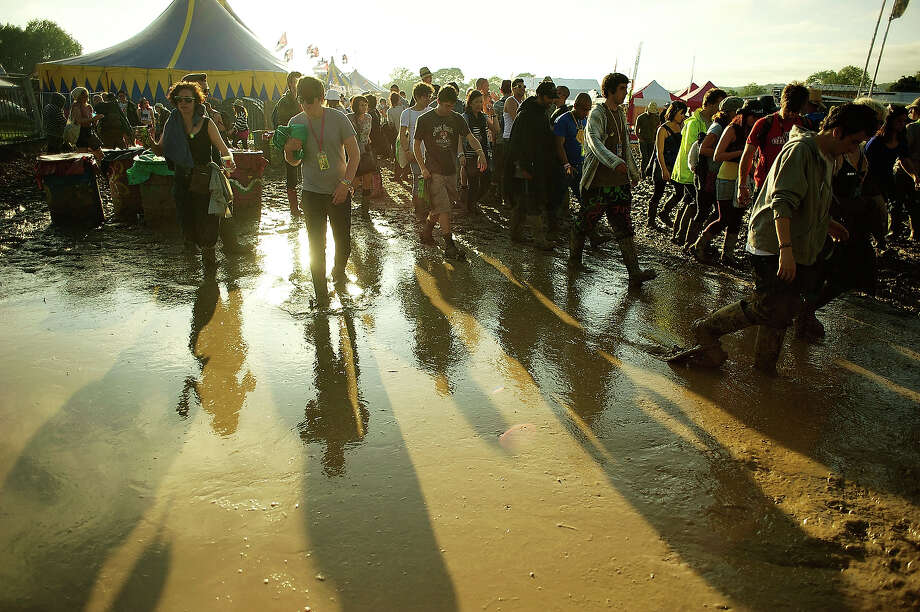 2011: Festival goers negotiate the mud in a general view of the festival site during the third day of Glastonbury Festival 2011 at Worthy Farm on June 25, 2011 in Glastonbury, United Kingdom. Photo: Felix Kunze, Redferns / 2011 Felix Kunze
