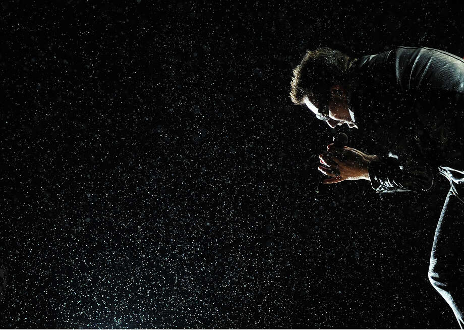 2011: Bono of U2 performs in the rain on the Pyramid stage during the Glastonbury festival near Glastonbury, Somerset on June 24, 2011. Photo: ADRIAN DENNIS, AFP/Getty Images / 2011 AFP