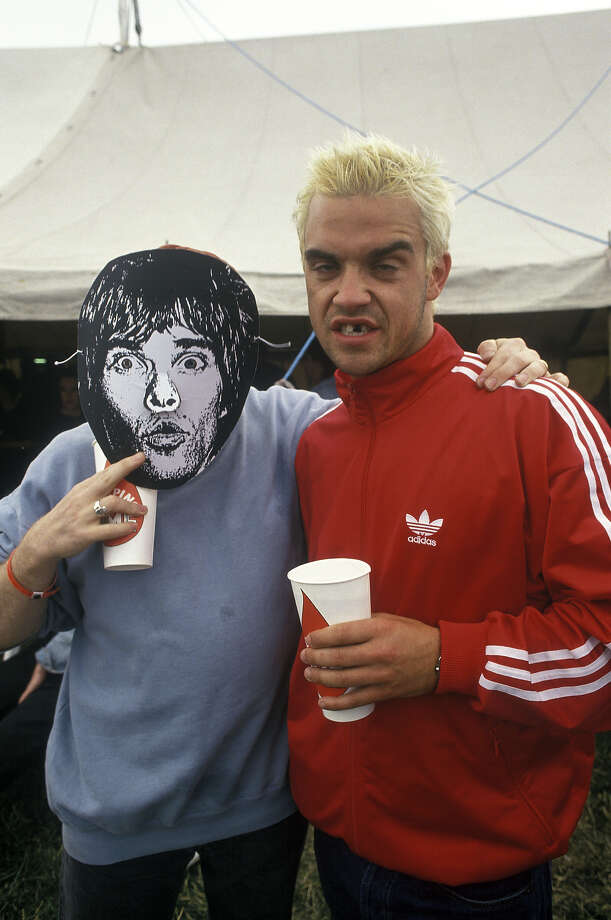 1995: Robbie Williams from Take That backstage at Glastonbury with a fan with a Stone roses Ian Brown Mask. Photo: Photoshot, Getty Images / 2012 Photoshot