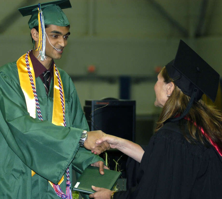 Tanner George receives his diploma from Board of Education chairwoman Wendy Faulenbach during New Milford High School's commencement exercises at the O'Neill Center on the campus of Western Connecticut State University in Danbury. June 22, 2013 Photo: Norm Cummings