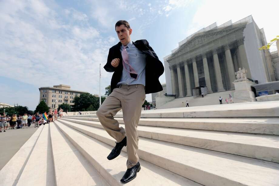 WASHINGTON, DC - JUNE 24:  Scotusblog.com intern Dan Stein runs with news of affirmative action ruling front of the U.S. Supreme Court building June 24, 2013 in Washington DC. The high court is expected to rule this week on some high profile decisions including California's Proposition 8, the controversial ballot initiative that defines marriage as between a man and a woman and an affirmative action case about the University of Texas admissions policy.