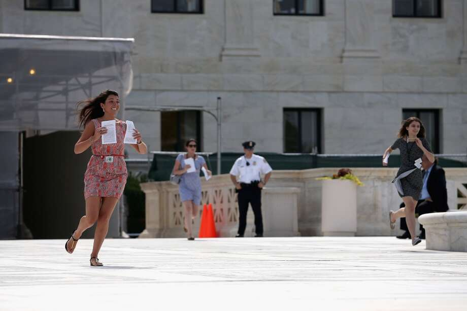 WASHINGTON, DC - JUNE 24: An employee with CNN  (L) runs after a ruling was made on race-based college admissions, in front of the U.S. Supreme Court building June 24, 2013 in Washington DC. The high court is expected to rule this week on some high profile cases including California's Proposition 8, the controversial ballot initiative that defines marriage as between a man and a woman and an affirmative action case about the University of Texas admissions policy.  (Photo by Mark Wilson/Getty Images)